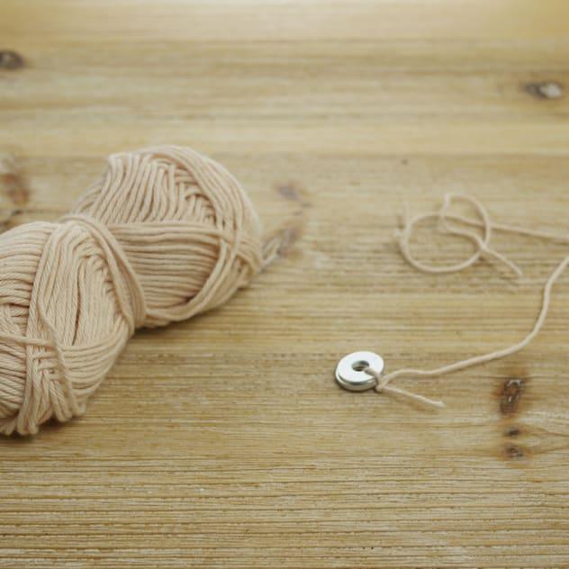 Cắt một đoạn dây cotton dài khoảng 40 cm và buộc một đầu dây vào một con ốc